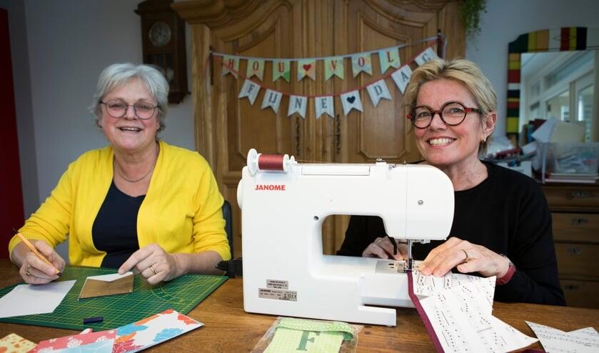 <p>Irma Botter (links) en Hellen Verhees maken vlaggenlijnen.</p>