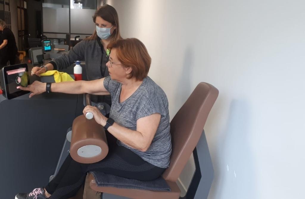 Happy Bodies clubmanager, Lisanne Bijnen (met mondkapje), helpt klant met instellen Milon cirkel.   Cis van Pinxteren © mooischijndel