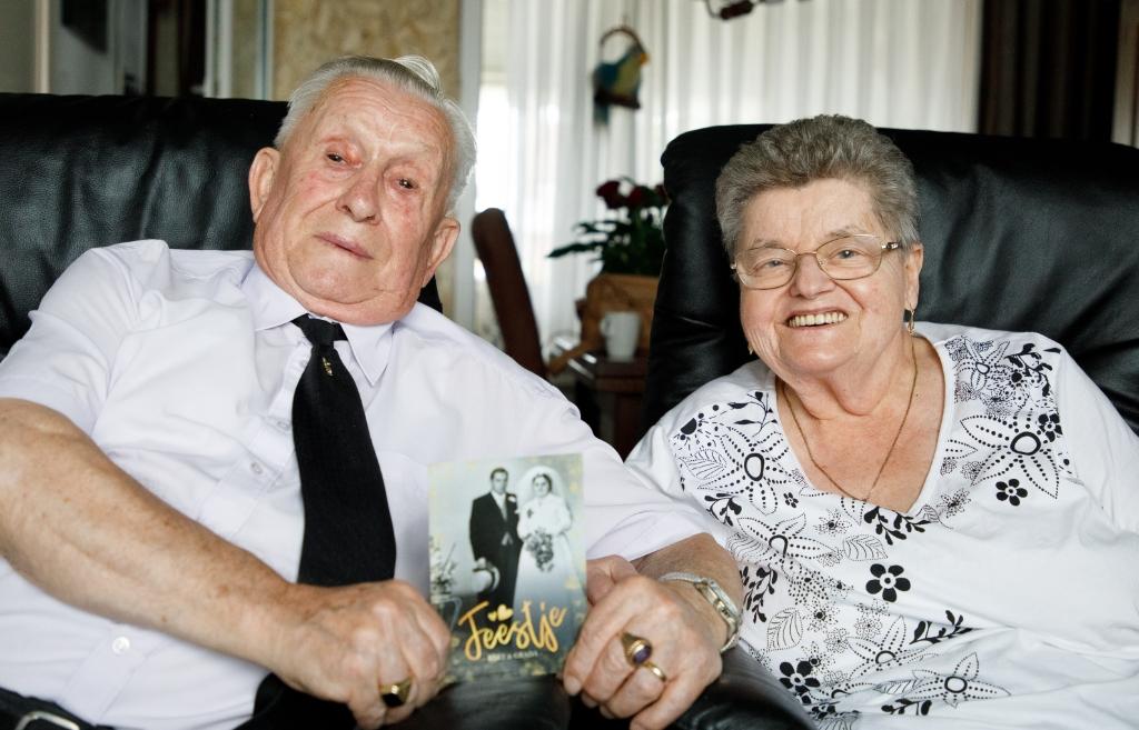 Bart (l) en Grada (r) met de uitnodiging waar hun zwart-witte huwelijksfoto de voorkant siert. Wiek van Lieshout © mooischijndel