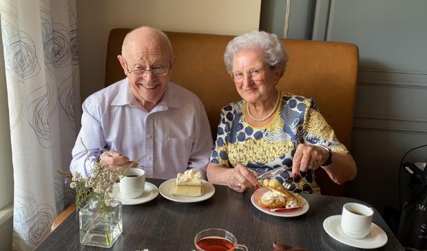 <p>Willy (l) en Diny (r) eten samen met zichtbaar genoegen gebak.</p>