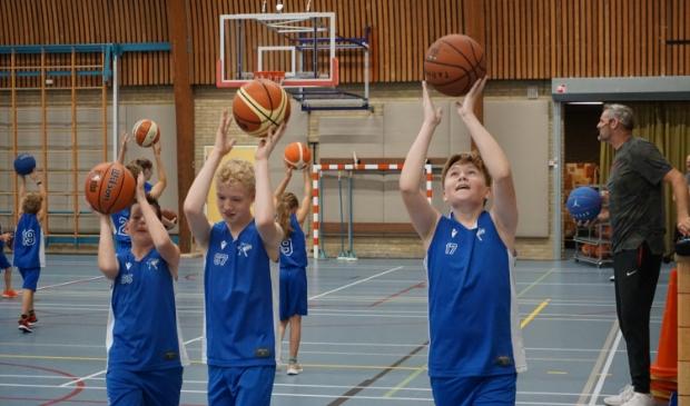 <p>Pieterse (r) houdt deze jonge basketballers scherp.</p>