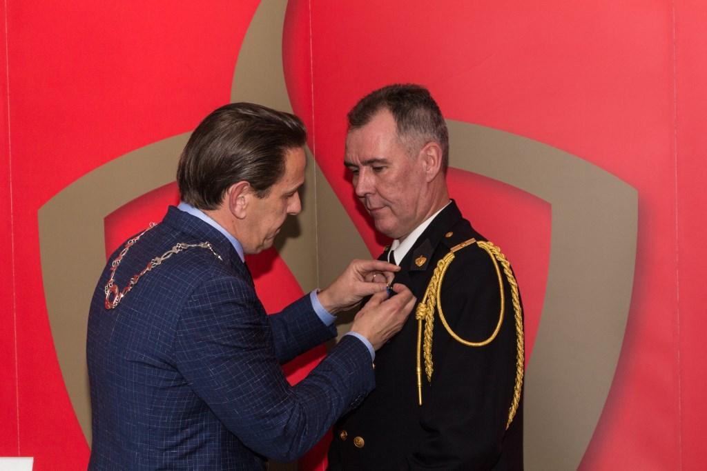 Dolf Mulder krijgt zijn lintje opgespeld door burgemeester Roland van Kessel Foto: Gonnie Feijen © grenskoerier