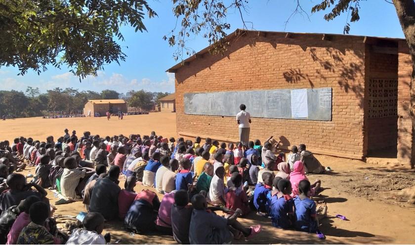 Vewwel leerlingen van de Chipala schoolkrijgen les in de open lucht