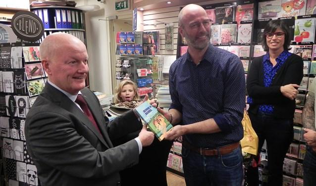 """Burgemeester Ruud van Bennekom neemt het eerste exemplaar in ontvangst van de bundel """"BUNNIK IN BUNDEL""""."""
