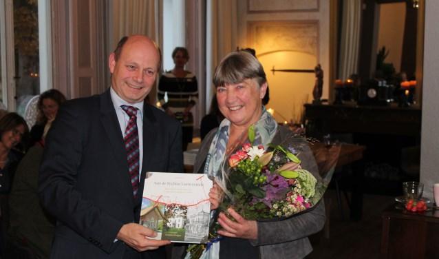 Loco-burgemeester Rob Jorg neemt het eerste exemplaar van het boek in ontvangst uit handen van auteur Annet Werkhoven.
