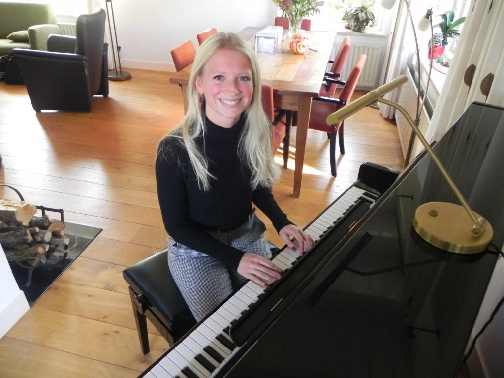 Christien achter de piano in haar ouderlijk huis waar ze zangles geeft aan haar leerlingen.