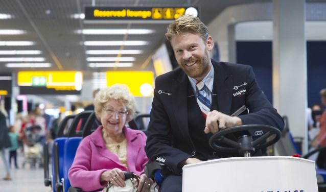 Passagiersassistenten rijden mensen die moeilijk ter been zijn naar de gate.