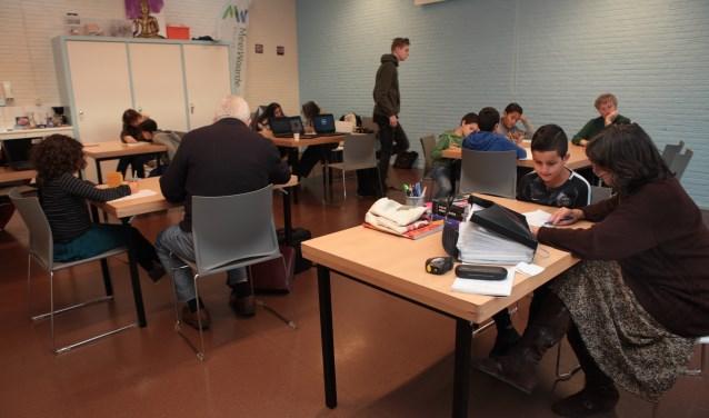 Vrijwilligers van Li Salaam helpen leerlingen met het maken van huiswerk.