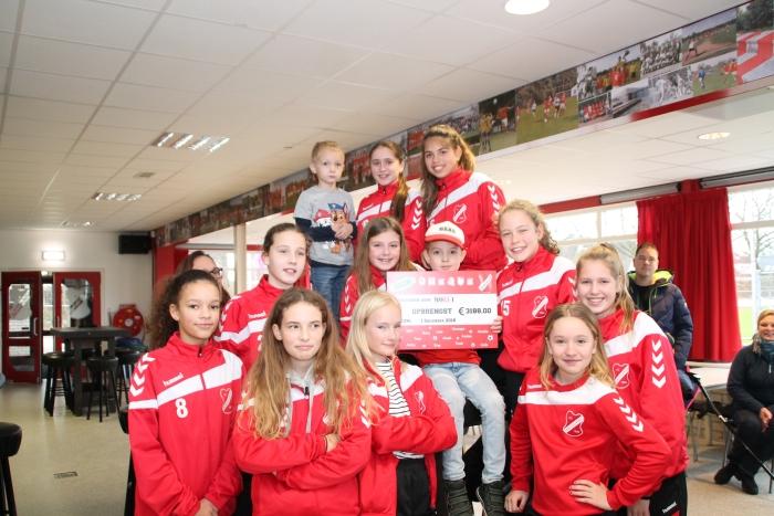 De speelsters van MO13-1 op de foto met Willem en de uitgereikte cheque.