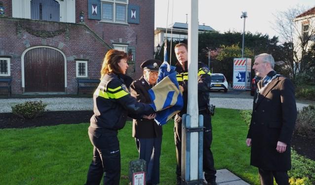 Oud-adjudant van de politie Wim Jansen hijst samen met wijkagent Leroy Vrijhoef de vlag bij het gemeentehuis.