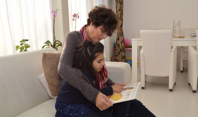 Sandra en de bijna 4-jarige Alveena samen op de bank tijdens het voorlezen.