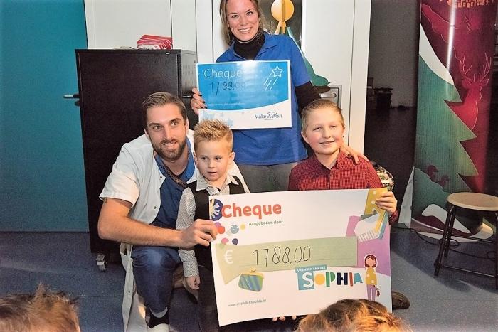 Blije kinderen geven een grote cheque voor zieke kinderen