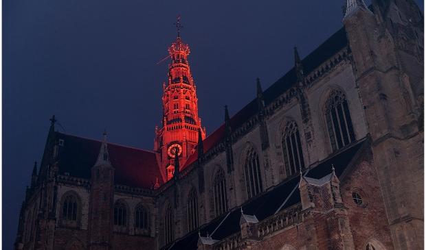 <p>De toren van de Grote of Sint - Bavokerk kleurt oranje.</p>