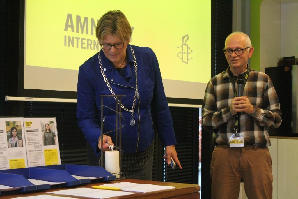 Burgemeester Cnossen en voorzitter Ruud van der Krogt steken de Amnestykaars aan. Hannie van de Veen © BDU media
