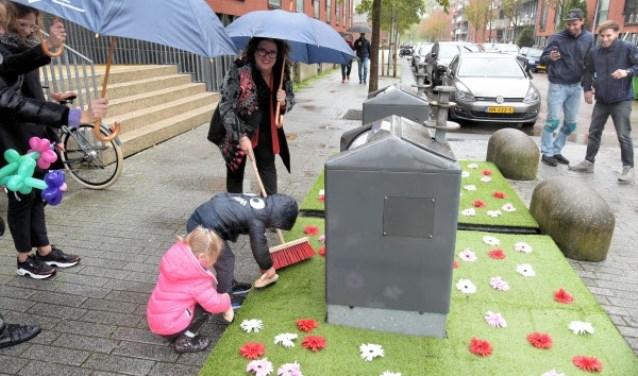 Wethouder Marjolein Steffens-van de Water borstelt samen met buurtkinderen de fleurige matten in Hoofddorp.