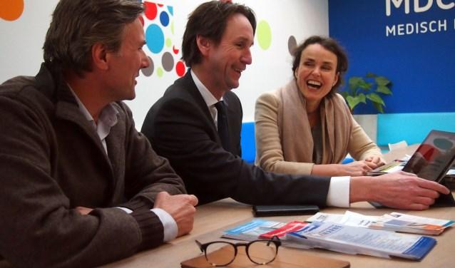 Wethouder Raat bekijkt met Roderik Kraaijenhagen en Sabine Pinedo Vital10 op een tablet.