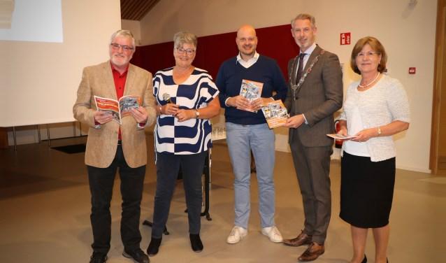 Burgemeester Hoes en de prijswinnaars van de fotowedstrijd ontvangen de eerste Dorpsgids editie 2018-2019