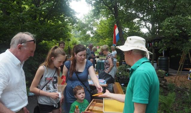 Imkers geven enthousiast uitleg over bijenwas en honing. De opening van de speciale tuin trok veel belangstelling.