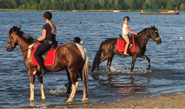 De meisjes genieten op de paardenruggen.