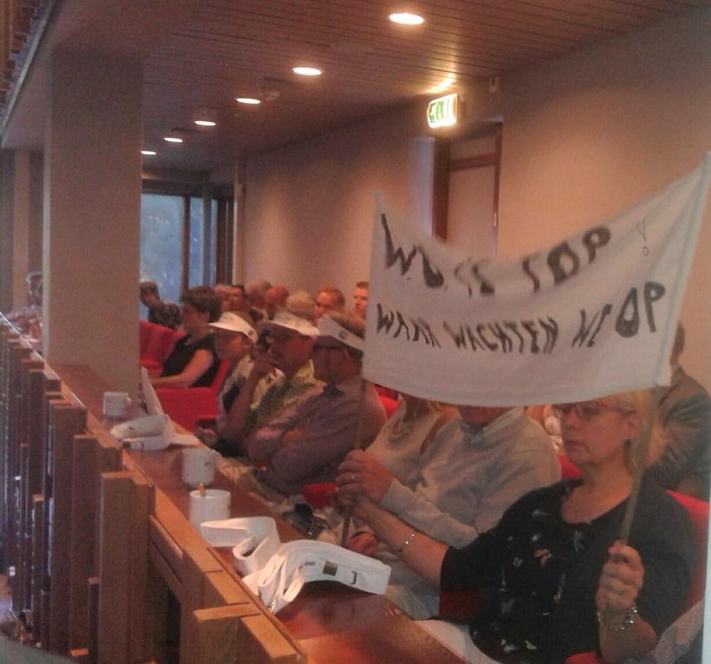demonstranten met spandoeken in de raadszaal.