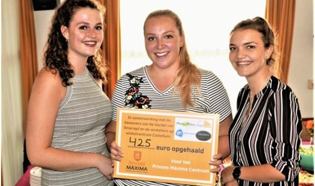 Lilian, in het midden, en twee vriendinnen tonen de cheque