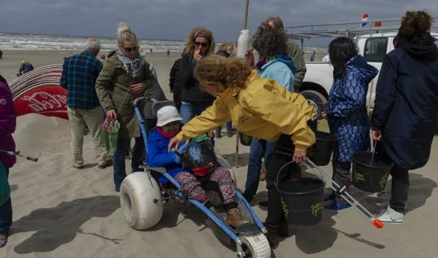 Marina in een strandrolstoel met gieter Tine op schoot voor de opgeraapte peuken Ellen Toledo © BDU media
