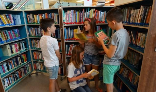 Lars, Job, Willemijn en Amélie van groep 7 van de Delteykschool zoeken boeken uit