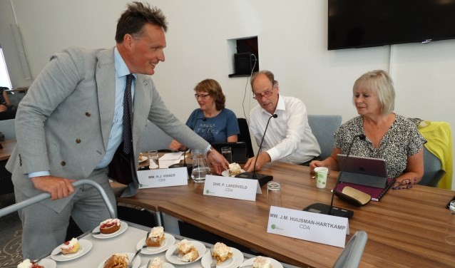 Wethouder Jorrit Eijbersen deelt gebak en koek uit aan de fractie van het CDA
