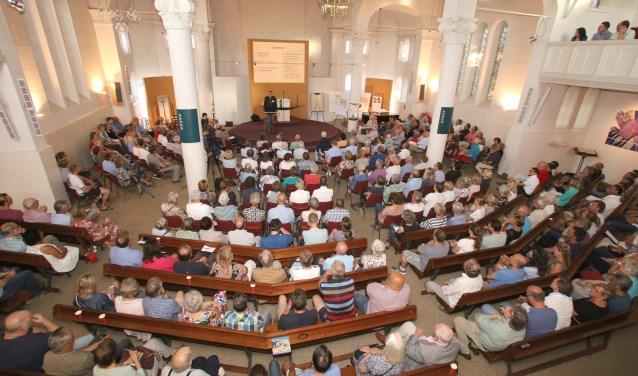 Een overvolle Paaskerk met belangstellenden voor het Baarnse erfgoed.