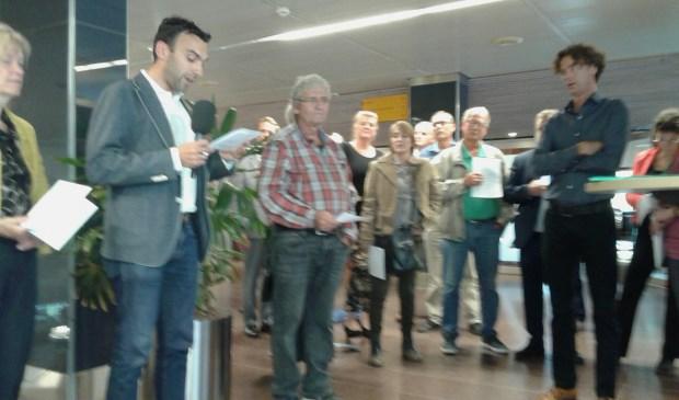 Christian van Barneveld (links, Groen in Amersfoort) overhandigt een petitie aan raadsvoorzitter Ben van Koningsveld (rechts).