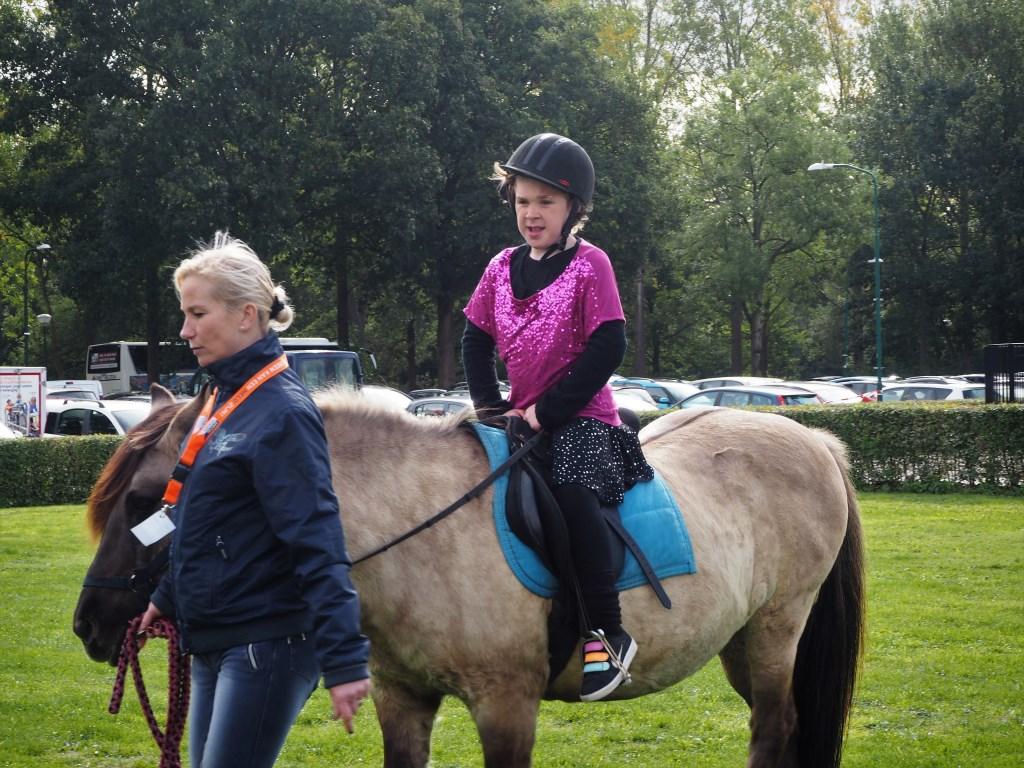 Lieveke, in haar danskleding, glunderend op een paard van Pegatrust.