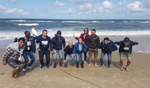 Nieuwkomers op het Vlielandse strand. Op het festival werkten de nieuwkomers samen met Nederlandse vrijwilligers.