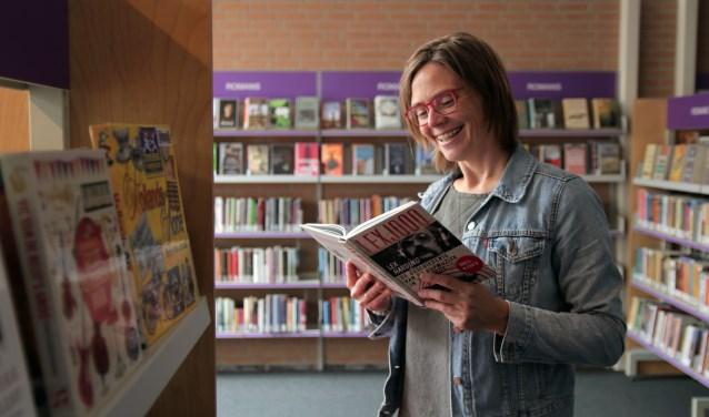 Thalita Boogaard van de bibliotheek snuffelt alvast even in een popgeschiedenisboek van Lex Harding.