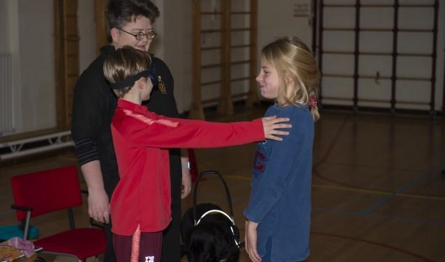 Dominiek Bos met haar geleidehond Nike laat kinderen met een blinddoek ervaren hoe het is om blind te zijn