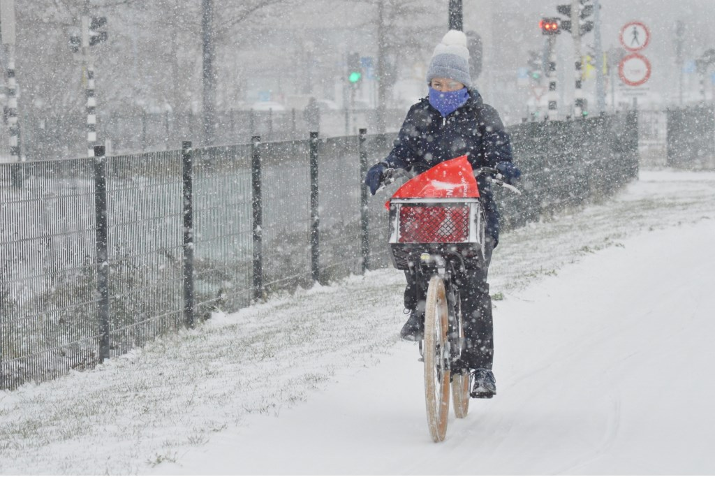 Een fietser trotseert dinsdagmiddag  een sneeuwbui.