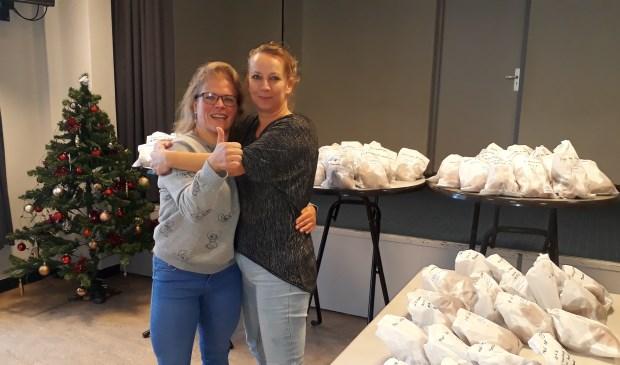 Sandy Schalk en Mariska Jansen tussen de oliebollen.