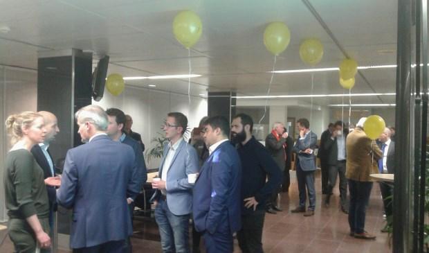 Tegenstanders van de rondweg (met gele ballonnen) spreken  politici in de wandelgangen.