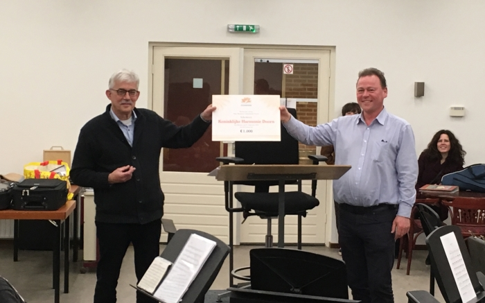 Voorzitter Huub Schouenberg (links) overhandigt cheque aan de dirigent Casper Dik (rechts)