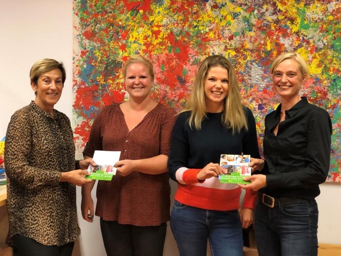 Oudercommissieleden van Stichting Peuterspeelzalen Hardinxveld-Giessendam ontvangen de eerste folder Spelen met een plus