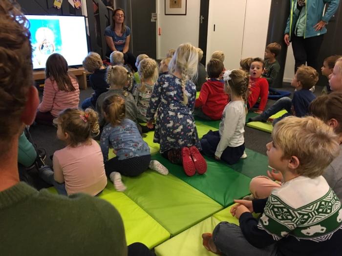 Ademloos luisteren naar Talitha, die Tim op de tegels voorleest tijdens de Kinderboekenweek De bibliotheek © BDU media