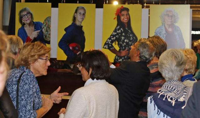 Bezoekers van de opening bekijken en bespreken de foto's van de heldinnen.