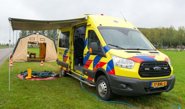 De HART-ambulance met op de achtergrond de tent waarin gewonden ontsmet en behandeld worden.