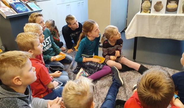 Kinderen luisteren geboeid naar verhalen over de Romeinse tijd