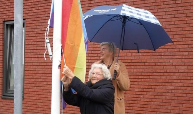 De 101-jarige Beppie van der Werf hijst de regenboogvlag.