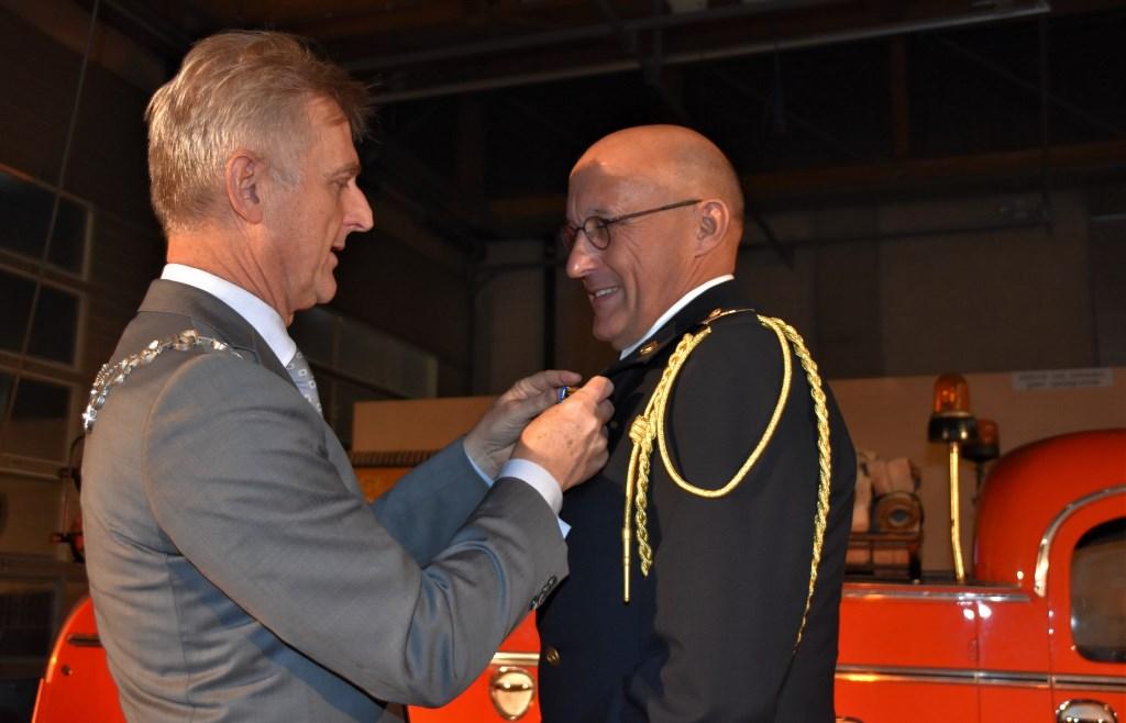 Burgemeester Rob Metz spelt de onderscheiding op bij Harrie Tolboom.