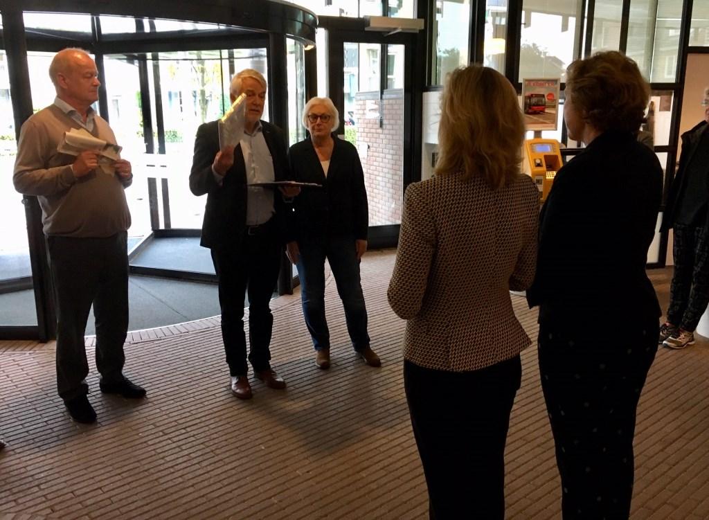 Een vertegenwoordiging van Burgerinitiatief Stop de Bomenkap biedt 3094 handtekeningen aan burgemeester Langenacker en wethouder Korrel aan.