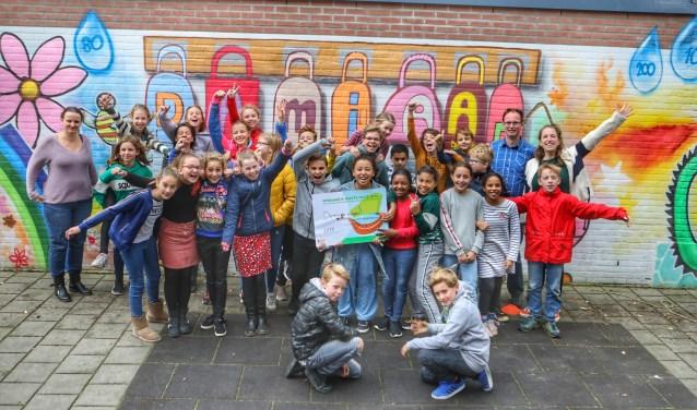 De leerlingen van de Damiaanschool met de cheque. Links recyclingcoach Sanne van RMN.