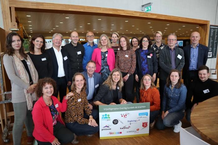 De leden van het Vrijwilligersplus Overleg poseren met wethouder Van Eijk (rechtsboven) na de ondertekening van de samenwerkingsovereenkomst.