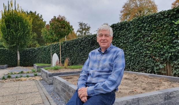 Cees op de rand van een lege plantenbak in zijn pas aangelegde tuin. Hij zoekt mensen die het op zijn kosten willen vullen.