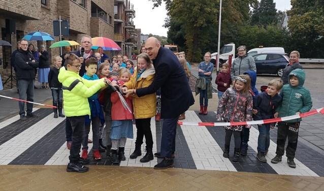 Samen met kinderen van Het Sterrenbos en De Regenboog knipt wethouder Gerrit Boonzaaijer het lint door.